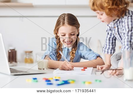 Gonna get an A. Pretty smart cheerful sister using help of her little brother making a creative representation of her home assignment while he carefully writing his sister writing formulas down