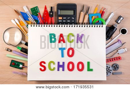 Back To School Text On Notebook Over School Supplies Or Office Supplies On School Table. Background