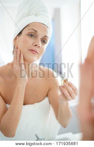 portrait of woman in bathroom applying moisturizing cream