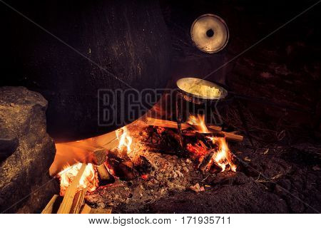 traditional cheesemaking - a huge pot of milk is heating up over a big wood fire. next to it, pasta is prepared in a smaller pot.