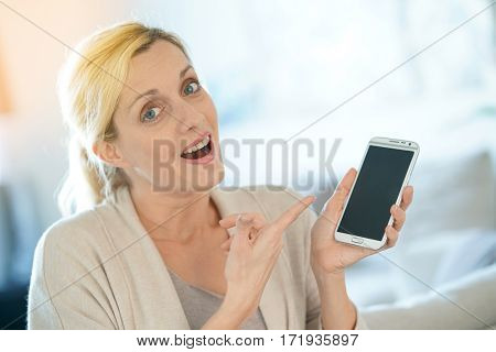 Blond woman pointing at message on smartphone screen