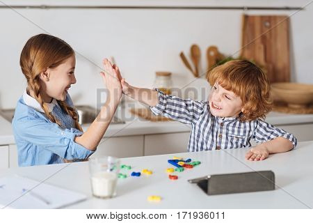 We make a great team. Clever sweet enthusiastic children accomplishing a math assignment using special game while having fun at the kitchen in the morning