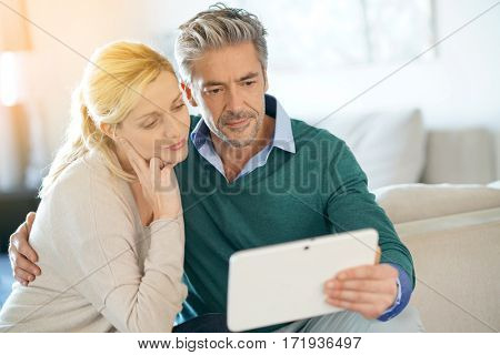 Couple at home websurfing with tablet