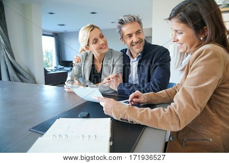 Real-estate agent reading terms of contract to clients