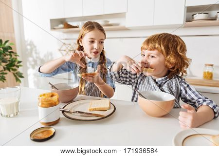 Just like mom. Charming nice young lady spreading some peanut butter on a piece of bread while her sibling tasting it and looking pretty pleased