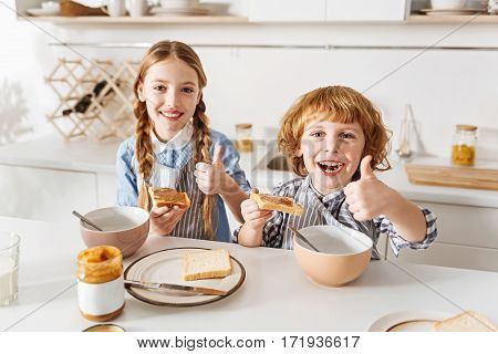Good start. Lively adorable enthusiastic siblings thinking that peanut butter sandwiches are rather delicious and being excited for the day while enjoying their morning meal
