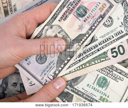 Human hand counting us dollar bills tender for all debts, public and private