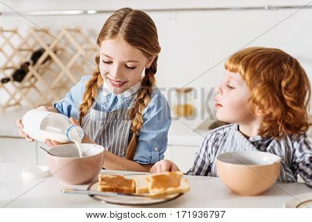 Easy cooking. Beautiful admirable lovely child sharing a morning meal with her brother and poring milk in her bowl while they both sitting at the table in a kitchen