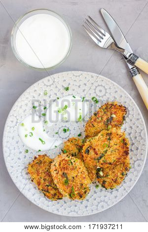 Vegetarian quinoa carrot coriander and green onion fritters served with yogurt on plate vertical top view