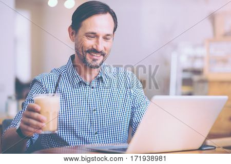 New start of the day. Cheerful handsome senior man sitting at the table and using laptop while resting in the cafe
