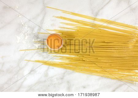 An egg and spaghetti pasta with traces of flour, shot from above on a white marble texture with a place for text