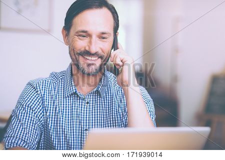 Its me. Cheerful delighted handsome man sitting at the table and talking on cell phone while resting in the cafe