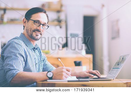 Find extraordinary in ordinary days. Positive delighted smiling senior man sitting at the table and managing his business matters while resting in the cafe