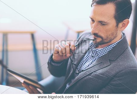 Let me think. Concentrated senior man usin gtablet and mulling over buisiness matters while sitting in the cafe