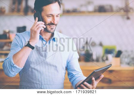 New ideas for my business. Cheerful senior smiling cafe owner talking on smart phone and managing his little business while expressing joy