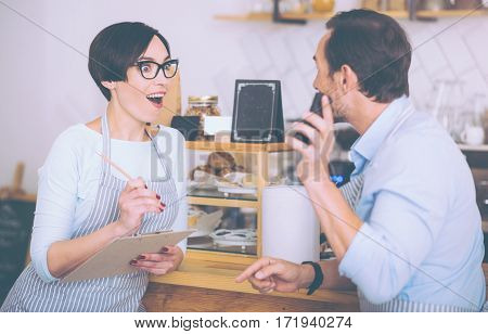 Eureka. Positive overjoyed couple standing near counter and discussing their business while running the cafe