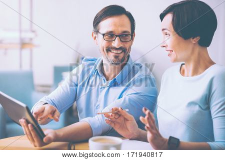 Emotional discussion. Pleasant professional colleagues sitting at the table and discussing business ideas while resting in the cafe