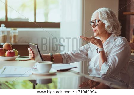 Online communication. Cheerful aged woman sitting in he kitchen and talking through the internet while sending kisses