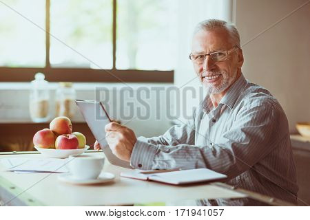 Nice beginning of the day. Cheerful smiling aged man using tablet and sitting in the kitchen while enjoying morning
