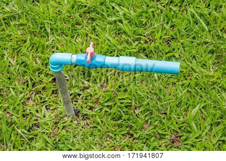 The faucet on green grass a background.