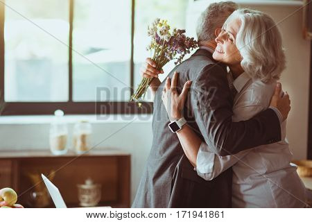 Close relationships. Overjoyed aged loving couple smiling and embracing while standing in the kitchen