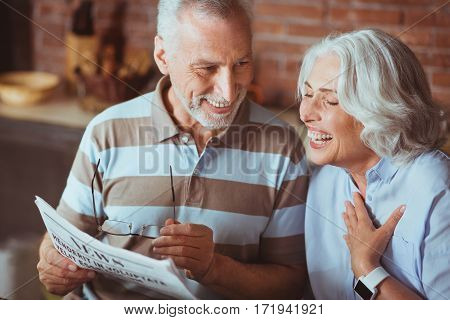 Full of emotions. Cheerful delighted smiling aged couple reading newsaper and sitting in the kitchen while resting at home