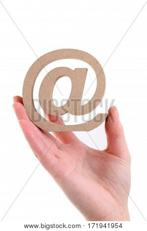 Hand holding wooden email symbol isolated on white background