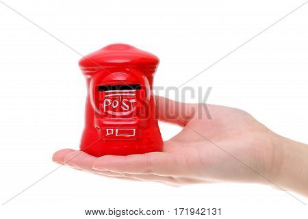 Red toy post box on the hand isolated on white background