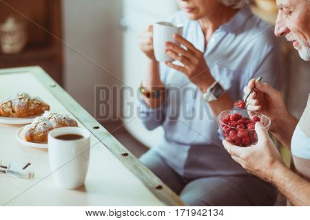 Everyday tradition. Pleasant loving aged couple sitting in the kitchen and having breakfast