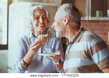 Love and care. Cheerful delighted smiling aged woman giving croissant to her husband while having breakfast together in the kitchen