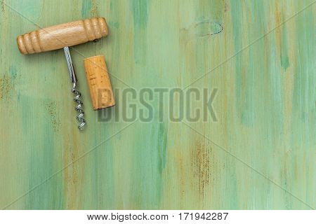 A photo of an old-fashioned corkscrew with a cork, shot from above on a green background texture with plenty of copy space. A design template for a wine list or a tasting invitation