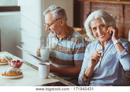 Full of gladness. Positive smiling aged woman talking on phone while enjoying morning with her husband in the kitchen
