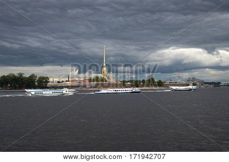 ST. PETERSBURG, RUSSIA - JULY 21, 2013: Tourist motor ships against the background of the Peter and Paul Fortress under the storm sky