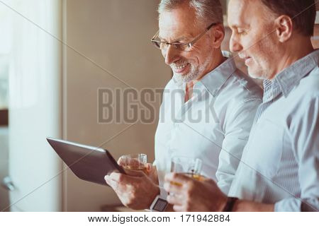 Share positivity. Pleasant content smiling aged friends standing in the kitchen and using tablet while resting together
