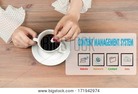 Content Management System concept. Coffee cup top view on wooden table background.