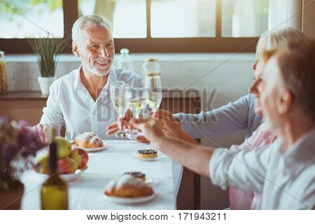 Full of joy today. Cheerful aged man making toast while sitting at the table with his family and having celebration