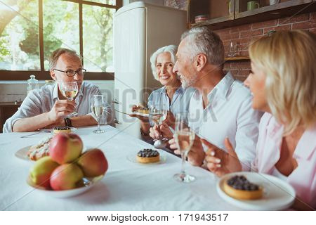 Enjoy the atmosphere. Cheerful content aged couples sitting at the table and having festive meal while resting at home