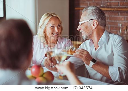Eternal family traditions. Cheerful smiling family sitting at the table and having celebration while resting at home