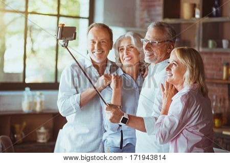 Memorize the moment. Cheerful aged family members holding selfie stick and taking photos while expressing gladness