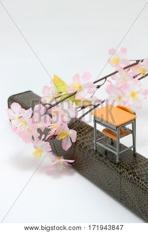 Study desk, diploma, and cherry blossoms on white background. Graduation concept.