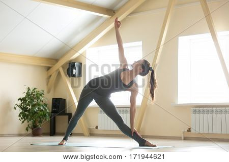 Young attractive woman practicing yoga, standing in extended triangle exercise, Utthita Trikonasana pose, working out, wearing sportswear, grey tank top, pants, indoor full length, home interior