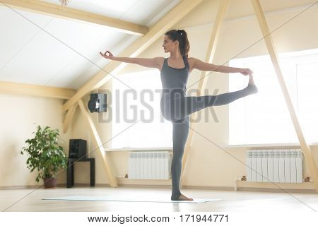 Young smiling woman practicing yoga, standing in Parivrtta Utthita Hasta Padangusthasana exercise, Twisting Extended Hand to Big Toe pose, working out, wearing grey sportswear, full length, home