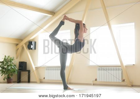 Young attractive happy woman practicing yoga, standing in Natarajasana exercise, Lord of the Dance pose, working out, wearing sportswear, indoor full length, home or sport club interior background