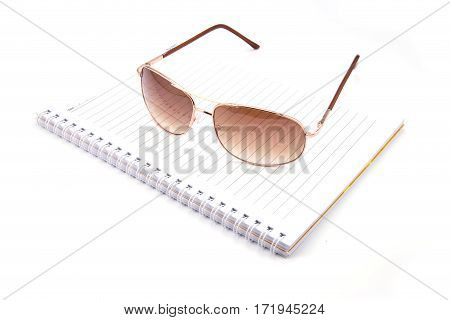 Sunglasses And Notebook Isolated Against A White Background