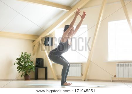 Young attractive happy woman practicing yoga, standing in Utkatasana exercise, Chair pose, working out, wearing grey sportswear, indoor full length, home or sport club interior background