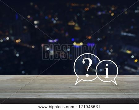 Question mark and information chat icon on wooden table over blur colourful night light city tower background Customer support concept