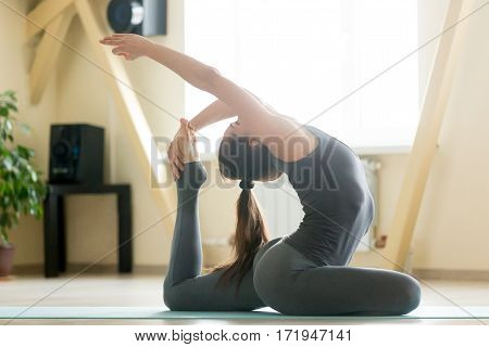 Young attractive woman practicing yoga, stretching in One Legged King Pigeon exercise, Eka Pada Rajakapotasana pose, working out, wearing sportswear, grey tank top, pants, indoor full length, room