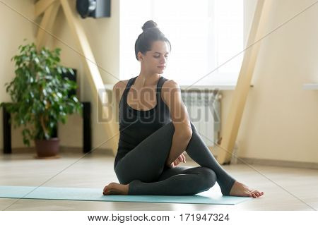 Young attractive woman practicing yoga, sitting in Half lord of the fishes exercise, Ardha Matsyendrasana pose, working out, wearing grey sportswear, indoor, home interior or sport club background