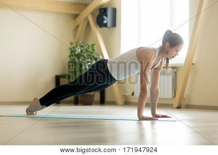 Young sporty serious attractive woman practicing yoga, doing Push ups or press ups exercise, phalankasana, Plank pose, working out wearing white tank top, black pants, indoor full length home interior