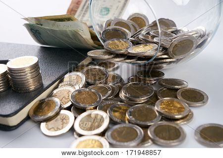 Business concept. Stack of coins, pen, paper money, notebook and glass piggy box isolated on white.